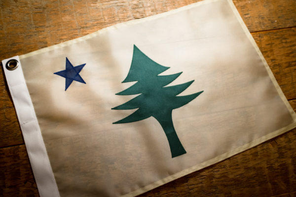 A finished original Maine flag, made by the Maine Flag Company in Portland, sits on a table in their studio last month. The  original flag sported just a pine tree and blue north star.