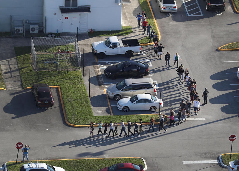 People are brought out of the high school Wednesday