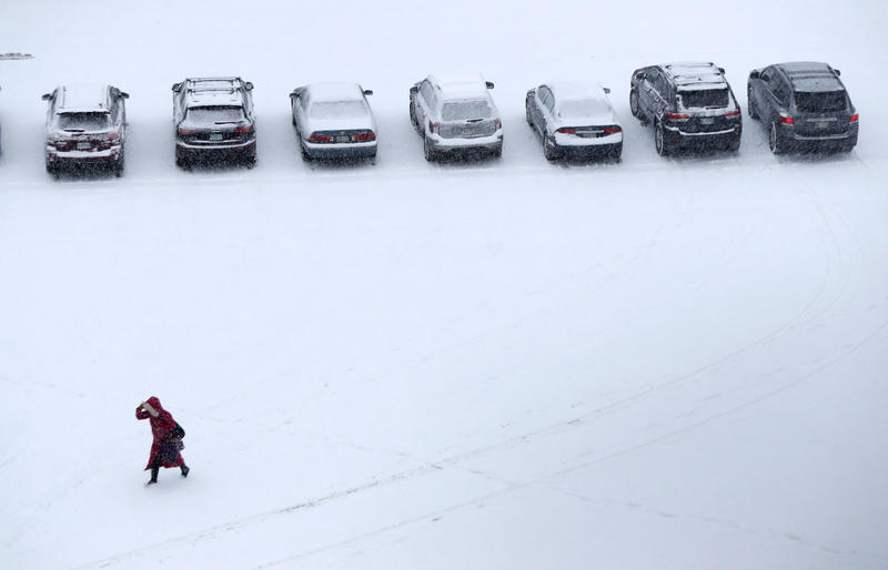 A woman makes her way across a snow-covered parking lot in Portland, Maine, Wednesday, Jan. 17, 2017.