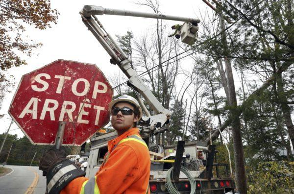 Canadian lineman Noah Clowater holds a bilingual stop sign while directing traffic while his coworkers restore power, Wednesday, Nov. 1, 2017, in Yarmouth, Maine.