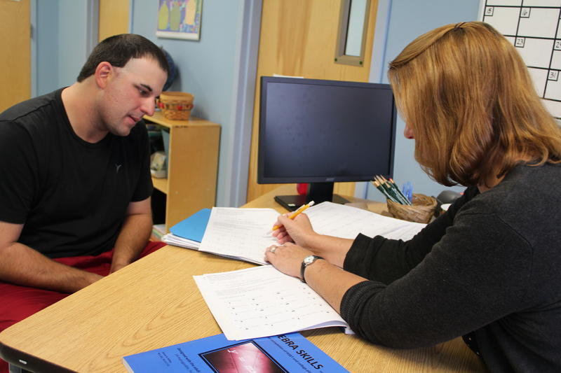 Teacher Betsy Bremner works with student Mozart Oliveira at Spruce Mountain Adult Education in Livermore Falls in a class designed to get students ready for the rigors of college