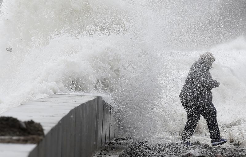 A woman gets caught by a wave as heavy seas continue to come ashore in Winthrop, Mass., Saturday, March 3, 2018.