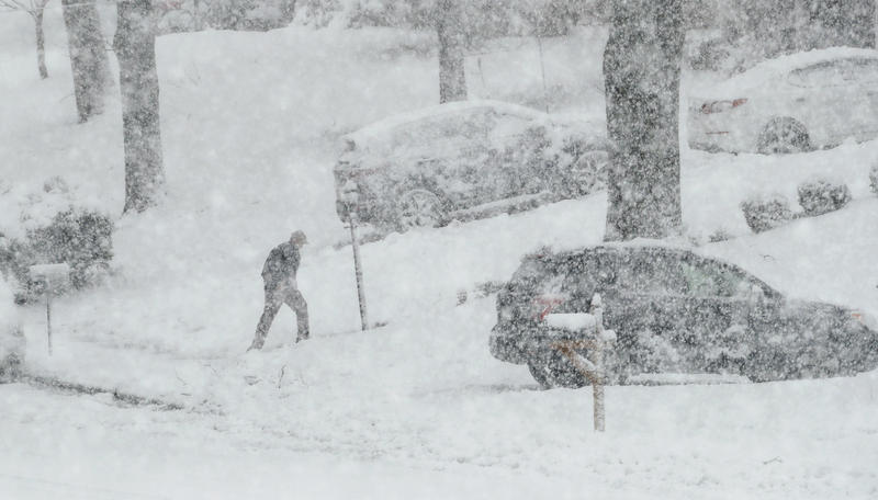 A man walks back from his mailbox during a winter storm, Wednesday, March 7, 2018, in Springfield, Pa.