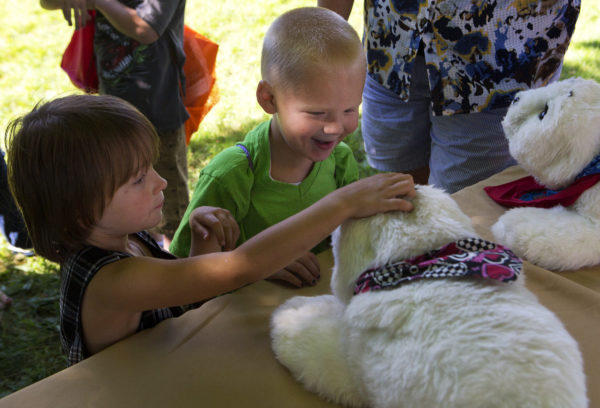 Kids in Bangor's Capehart neighborhood touch a robotic seal during a back-to-school block party in August 2016 sponsored by Community Partnerships for Protecting Children.
