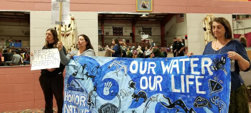 Members of the Penobscot Nation display a banner at a political forum Wednesday night on Indian Island.
