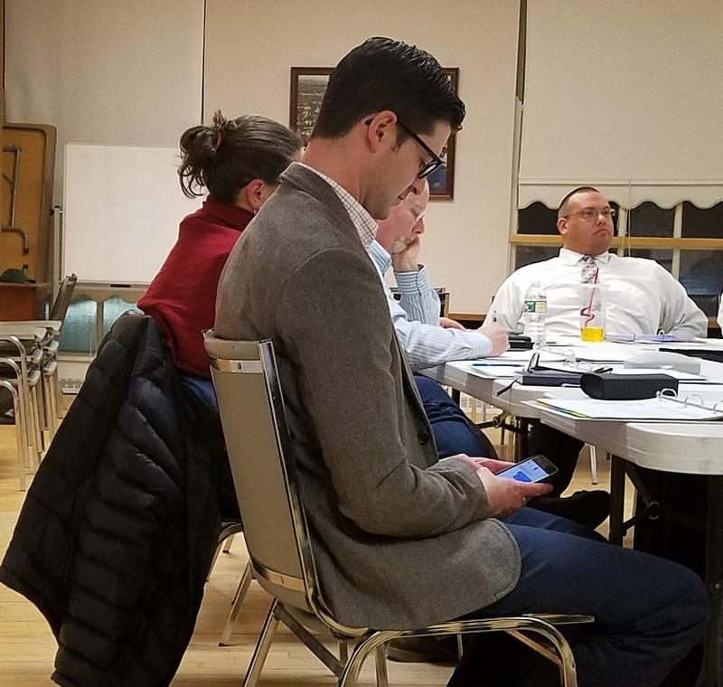 Waterville Mayor Nick Isgro texts Tuesday evening during a City Council budget workshop.
