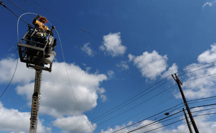 Scott Cornforth, a foreman with NextGen, installs a guy wire on a utility pole as part of the installation of the statewide middle-mile fiber-optic network called the Three Ring Binder, in 2012.
