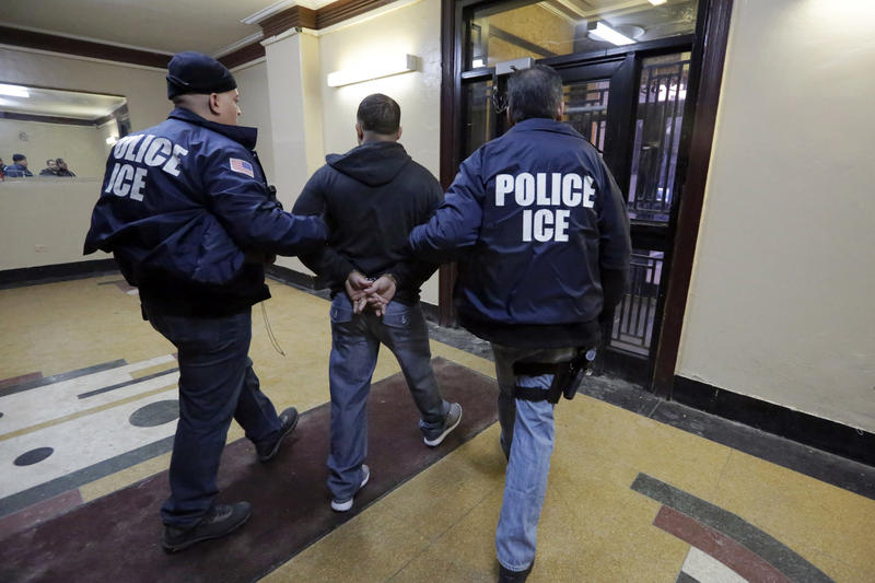 In this March 3, 2015 photo, Immigration and Customs Enforcement officers escort an arrestee in an apartment building, in the Bronx borough of New York, during a series of early-morning raids.