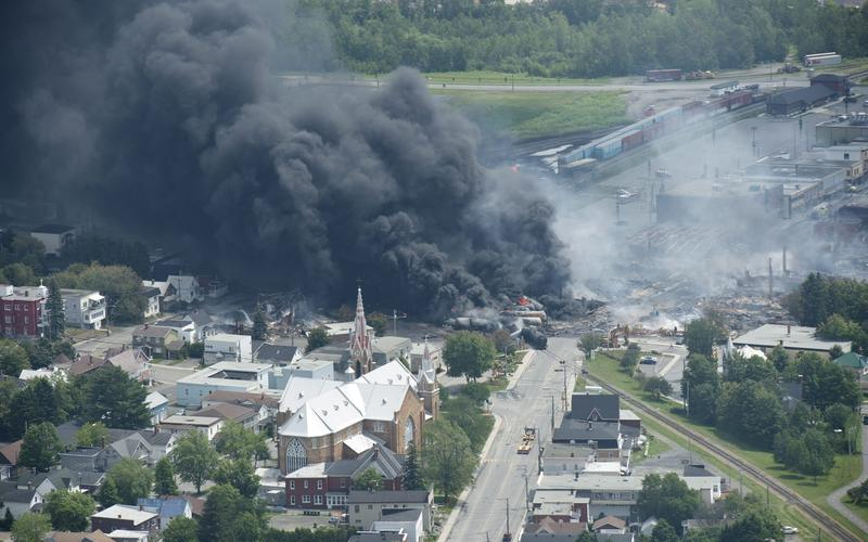 Smoke rises from railway cars that were carrying crude oil after derailing in downtown Lac Megantic, Quebec, Canada, Saturday, July 6, 2013.
