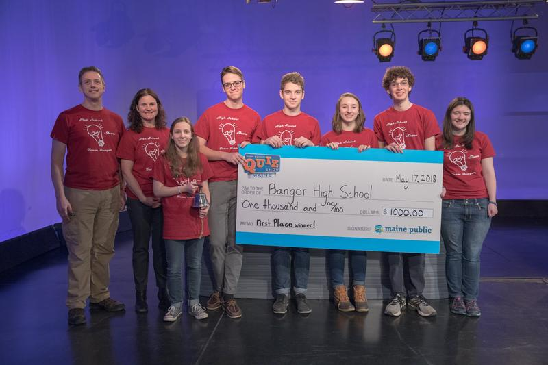 The Bangor High School team holds their $1,000 check for their school's Project Graduation as well as a replica school bell created by Richard Fisher of U.S. Bells and Tim Fisher of Fisher Woodworking in Prospect Harbor after winning season two of High Sc