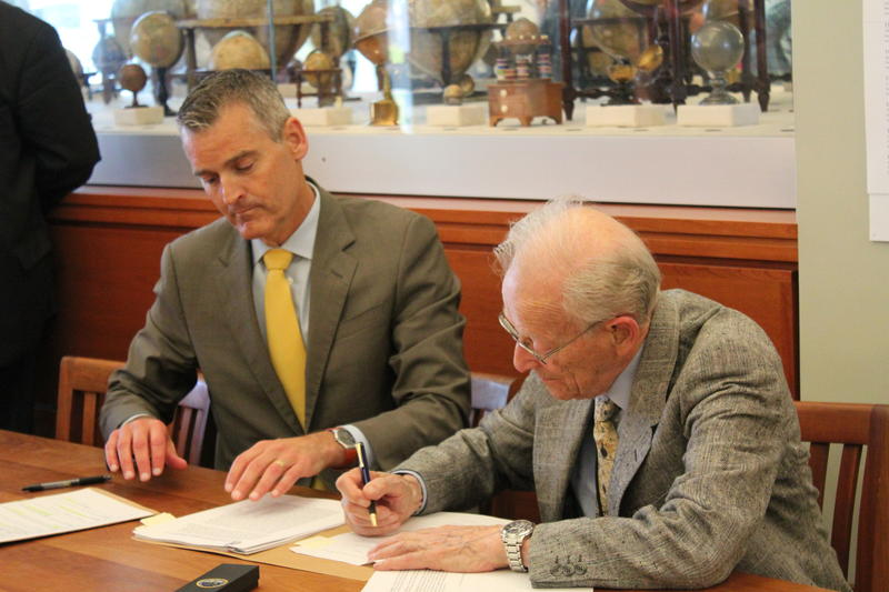 Dr. Harold Osher and University of Southern Maine President Glenn Cummings sign documents agreeing to Osher's donation of more than 450,000 maps to the university.