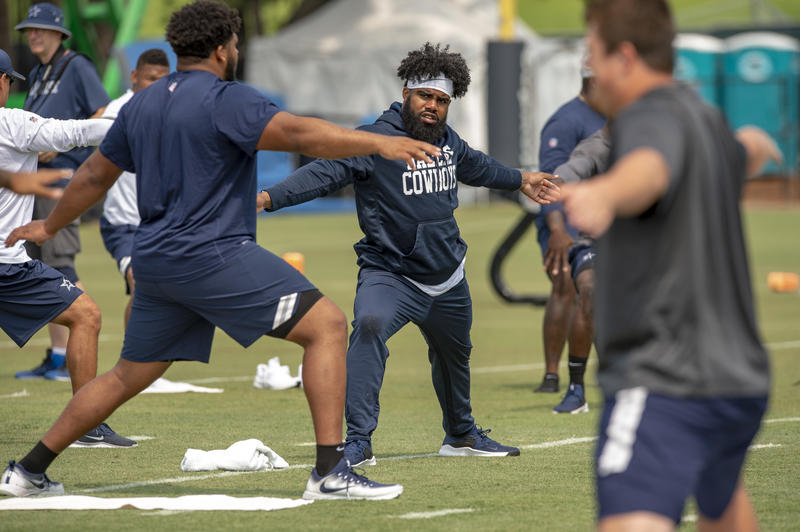 Dallas Cowboys offensive tackle La'el Collins (left) and teammate running back Ezekiel Elliott (right), do yoga for flexibility during NFL football training camp, Saturday, July 28, 2018, in Oxnard, Calif.