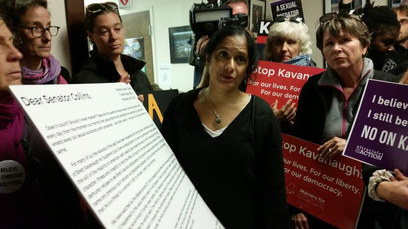 Dini Merz of Mainers for Accountable Leadership, presents the letter to a Collins staff person at the office in Downtown Portland.