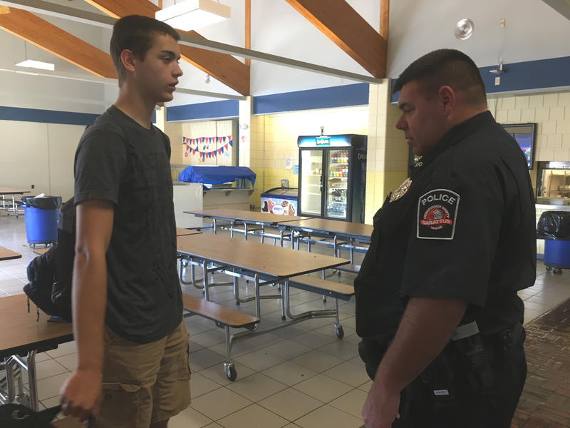 RSU 4 school resource officer John Dalbec speaks with a student in the cafeteria of Oak Hill High School in Wales.