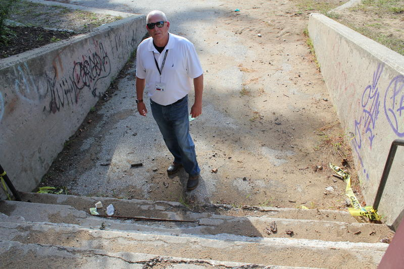 Portland Public Schools Facilities Manager Steven Stilphen peers into the back entrance to Longfellow Elementary School, with with deteriorating concrete along the back steps.
