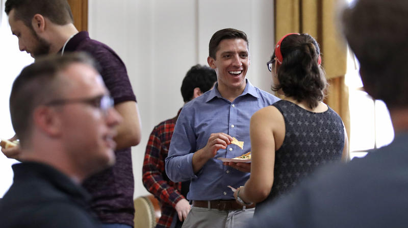 Zak Ringelstein, center, a Democratic candidate for U.S. Senate in Maine, eats a potluck dinner during a gathering prior to a meeting of the Southern Maine Democratic Socialists of America at City Hall in Portland, Maine, Monday, July 16, 2018.