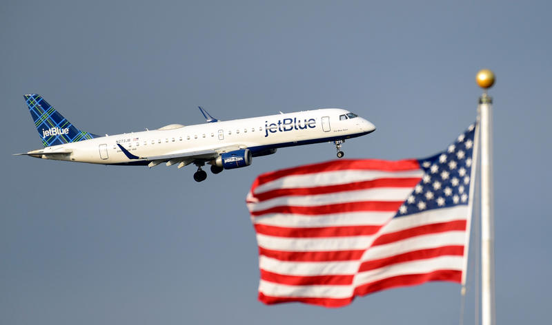 A plane flies past the American flag in Washington, Friday, Sept. 21, 2018.