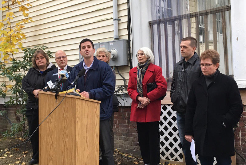 Maine Affordable Housing Coalition Director Greg Payne announces a new lead abatement program, flanked by current and former lawmakers, and landlord Amy Smith.