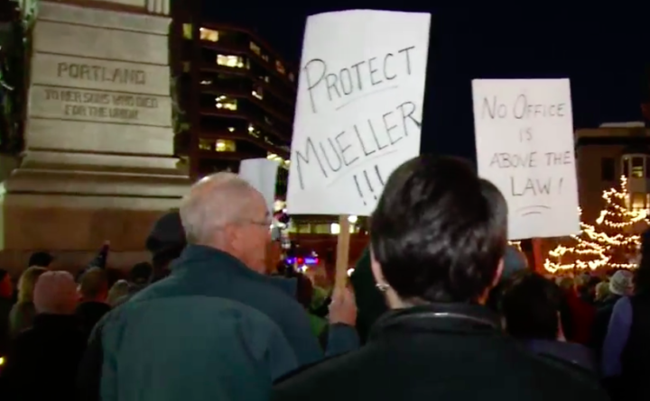 Demonstrators hold signs in Portland's Monument Square Thursday night.