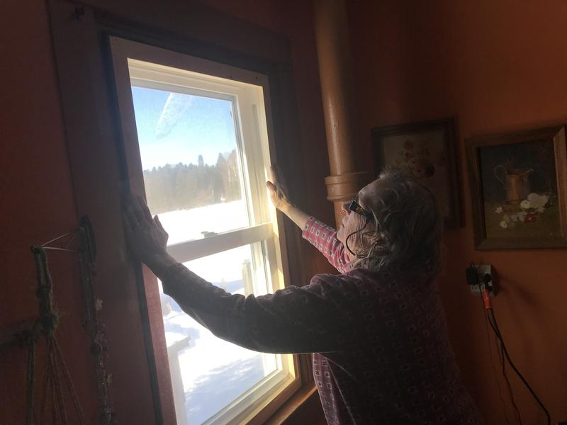 Catherine Reed hand-tightens a customized window-insert at her Moose River farmhouse.