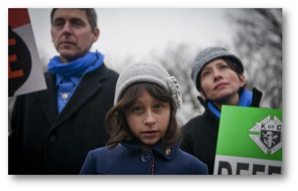 "Lucia Dragas, 8, from Boston, Mass., held a poster saying ""Defend Life"" along with her parents during a March For Life rally held in Washington D.C., on January 25, 2013."