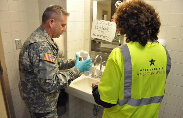Members of the West Virginia National Guard's Chemical, Biological, Radiological, Nuclear and High-Yield Explosive Enhanced Response Force Package draw water sample to determine levels of contamination.