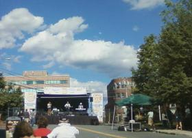 A gathering crowd watching a stage set up in the middle of the street in Nashua