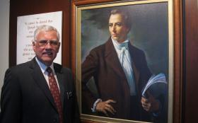 Elder Brian Schuck stands next to a portrait of Mormon prophet Joseph Smith.