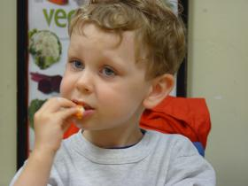 A student at Keene State's Early Learning Center samples the yogurt dip.