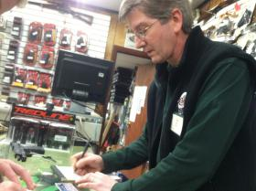 Doug Dack, a manager at Riley's Sport Shop in Hooksett, fills out paperwork during a sale Monday.