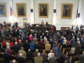Legislators and audience members bow their heads for the pledge of allegiance, before the Governor's address.