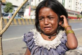 According to Oxfam, the world's poor spend three-quarters of their income on food. A survey by Save the Children found that 24 percent of families in India, 27 percent in Nigeria and 14 percent in Peru now have foodless days. Pictured: A young girl in India cries for food.