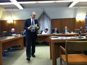 Insurance Department Deputy Commissioner Alex Feldvebel hands out documents during today's oversight committee meeting.