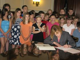 Governor Hassan makes it official, with some help from Derry Village Elementary School 4th graders.