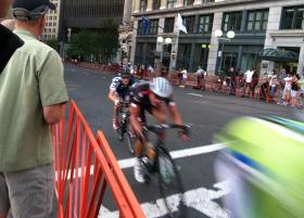 Riders at the front of the race in the Mayor's Cup rush past the barriers that surround Government Center.