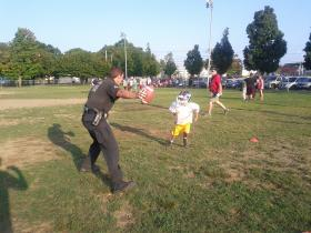 A Manchester police officer helps out with football practice.