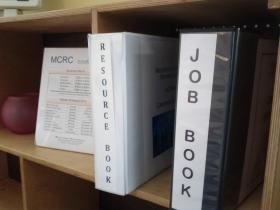 The MCRC tries to make it easy for adults (including immigrant and refugee parents) to get jobs in the area. One way they do this is by having staff members compile a list of jobs and putting it in a binder called a 'Job Book.'