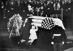 Jackie and her daughter Caroline kneel before John F. Kennedy's coffin.