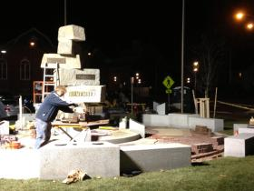 Workers work to finish constructing the new Memorial Park monument late Friday night.