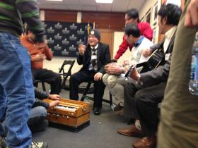 Bhutanese community leaders singing and dancing to their traditional music during a workshop lunch break.