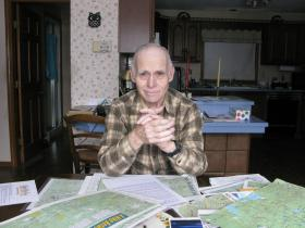 Dave Roberts has spent his entire retirement mapping the Belknap Range. His maps which are sold for a pittance at area libraries, map many peculiarities and historical oddities. Like a plane crash on Mount Belknap, and a tree that over the years has grown around a cross-cut saw that was left leaning against it.