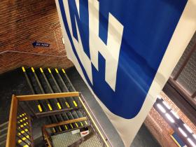 A giant banner with the new UNH logo now hangs in the front stairway of 400 Commercial st, UNH Manchester's university center.