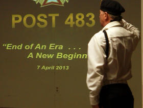 A member of VFW Post #483 is silhouetted as he salutes the flag during closing ceremony on April 7, 2013, in front of a slideshow depicting the 92-year history of the post.