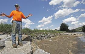 Doug Turner stands along the rebuilt river bank of the Mad River at his farm in Waitsfield one year after Irene.