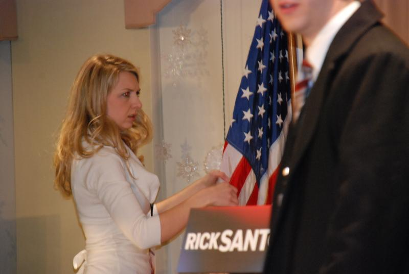 Santorum staffers adjust the American flag at the podium where the candidate is expects to appear later this evening.