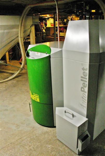 The OkoFEN is about the size of a conventional oil boiler. The storage bin behind the unit - which looks like a huge and fancy laundry basket - holds wood several tons of pellets which are automatically fed into the boiler.
