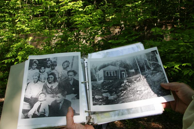 Behind the photos of the old school - and its students - the foundation is almost hidden by the forest.
