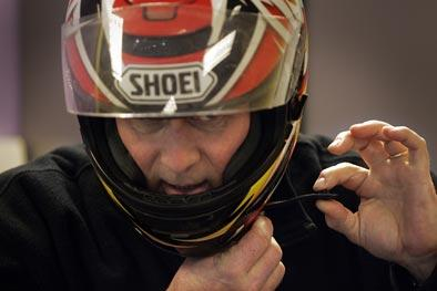 Assistant instructor Pete Sperling demonstrates the proper way to put on a helmet and adjust the strap during Friday night's part of the three day weekend NHDMV motorcycle training course.