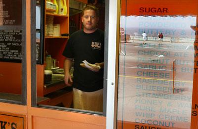 The beach is reflected in the Blink's Fried Dough wall menu as fry dough cook Scott Graham of Exeter serves up an all time favorite with cinnamon and powdered sugar.