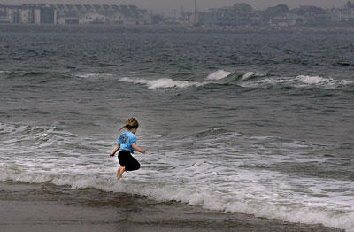 A little girl jumps the cold waves.